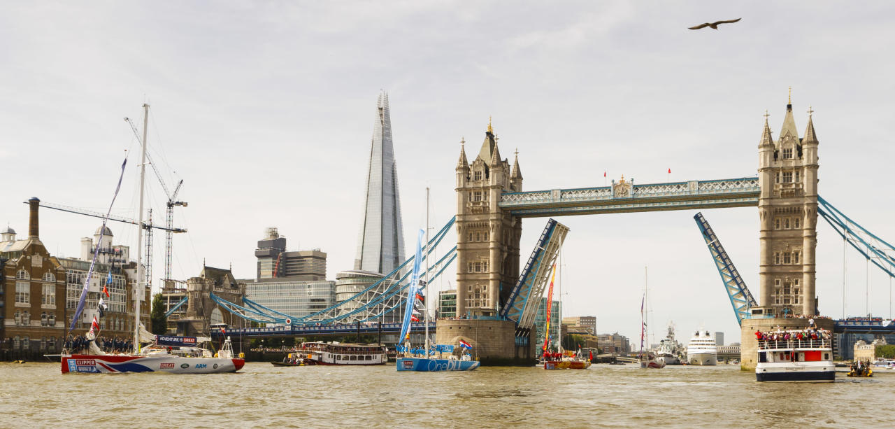 The Great Britain Clipper, leads four of the twelve Clipper Round the World Race yachts through Tower Bridge during the start of the Clipper Round the World Race at St Katharine Docks, London.