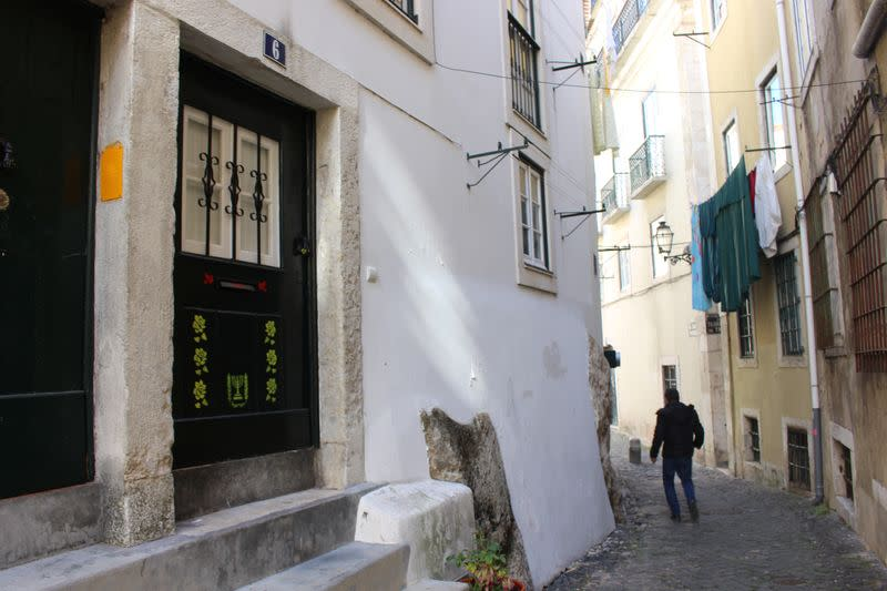 A man walks down an alley in the former Jewish quarter in one of LisbonÕs most historic neighbourhoods of Alfama