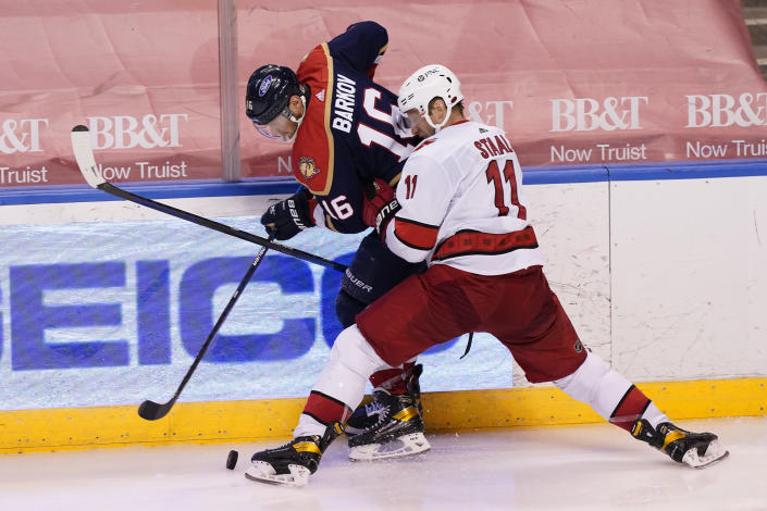 Carolina Hurricanes center Jordan Staal (11) and Florida Panthers center Aleksander Barkov (16) fight for the puck during the third period at an NHL hockey game, Saturday, Feb. 27, 2021, in Sunrise, Fla. (AP Photo/Marta Lavandier)