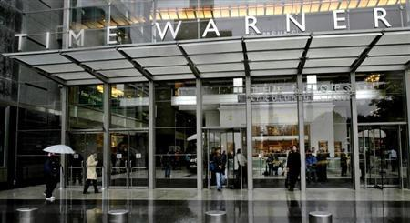 People walk in front of the Time Warner Inc. headquarters building at Columbus Circle in New York