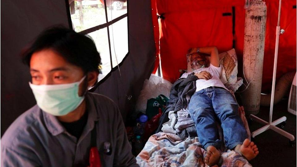 Ketut Nomer, a 59-year-old patient suffering from coronavirus disease (COVID-19), rests as his 28-year-old son Gede Zico sits taking care of him, at a temporary tent outside the emergency ward of a government hospital in Bekasi, on the outskirts of Jakarta, Indonesia, 25 June 2021.
