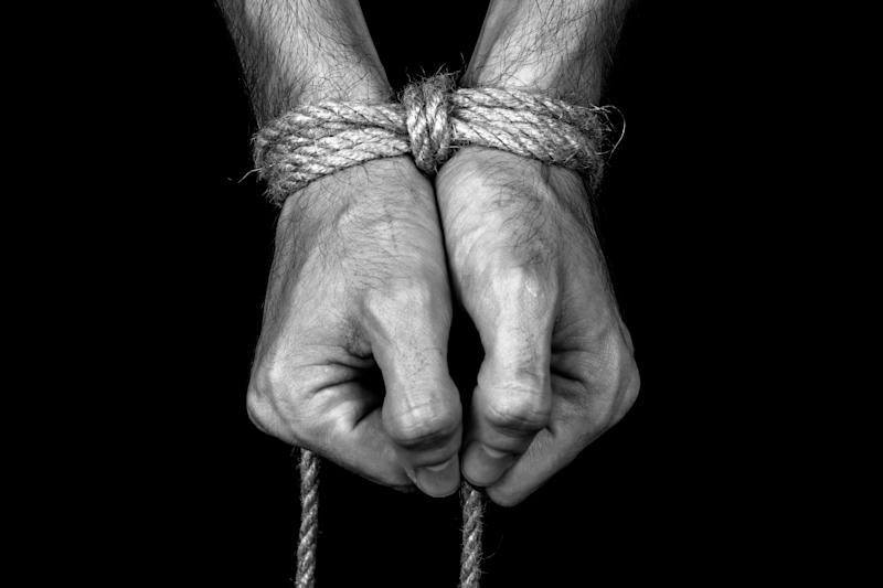 Hands tied with rope. (Photo: Getty Creative)