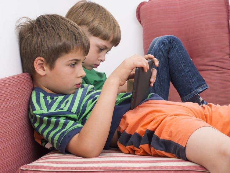 Two boys slumped on a sofa, holding tablet computers