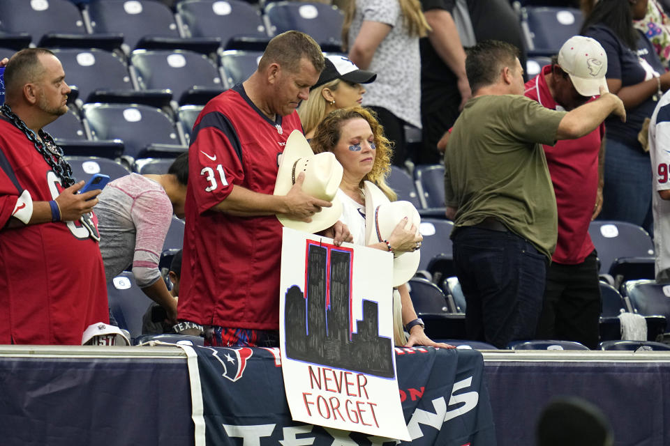 Houston Texans fans bow their heads during a 9/11 memorial video before an NFL football game against the Jacksonville Jaguars Sunday, Sept. 12, 2021, in Houston. (AP Photo/Sam Craft)