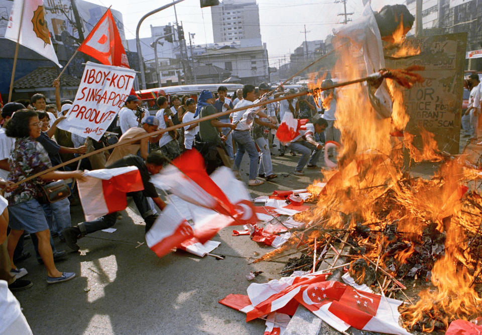 FILE PHOTO: Protesters burn Singaporean flags during a rally, Saturday, March 25, 1995 near the Presidential palace in Manila to protest the execution in Singapore of Filipino maid, Flor Contemplacion. (AP Photo/Pat Roque)