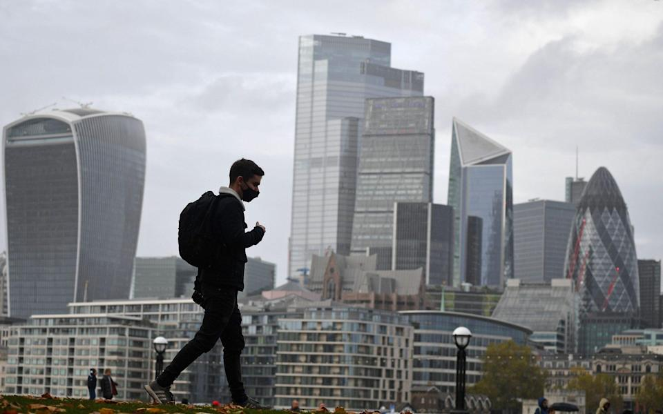 A man walks along the southern bank of the River Thames with the office towers of the City of London in the background