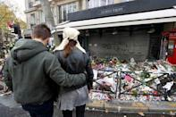 A couple share a quiet moment in front of flowers, candles and messages in tribute to victims in front of the La Belle Equipe cafe, one of the sites of the deadly attacks in Paris, France, November 17, 2015. REUTERS/Jacky Naegelen