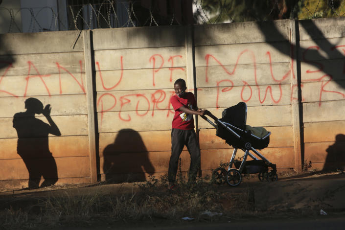 "A young boy pushes a pram past a wall with graffiti advocating for People Power ,on the streets of Harare in this Tuesday, July, 7, 2020 photo. Unable to protest on the streets, some in Zimbabwe are calling themselves ""keyboard warriors"" as they take to graffiti and social media to pressure a government that promised reform but is now accused of gross human rights abuses.(AP Photo/Tsvangirayi Mukwazhi)"