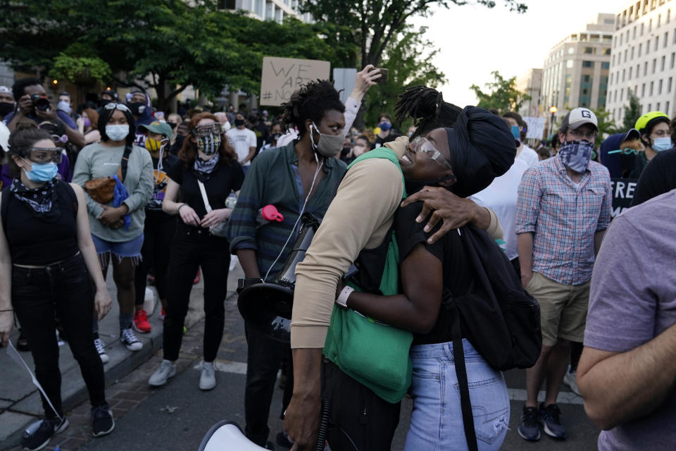 People hug as demonstrators gather to protest the death of George Floyd, Tuesday, June 2, 2020, near the White House in Washington. Floyd died after being restrained by Minneapolis police officers. (AP Photo/Evan Vucci)