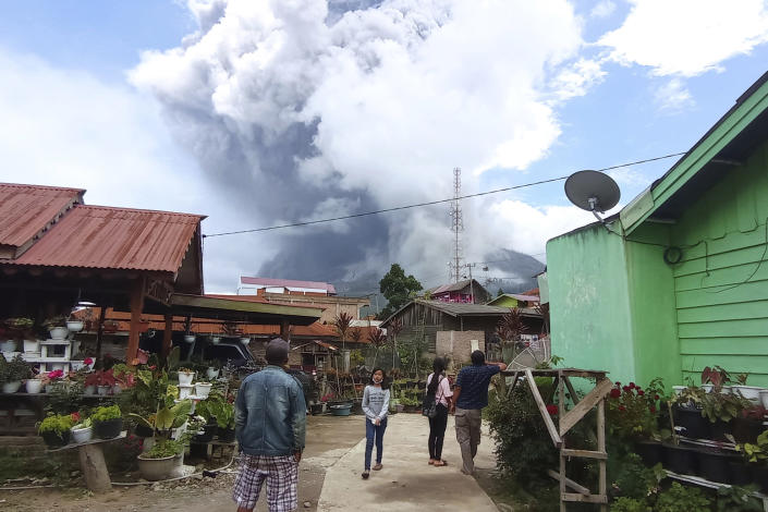 People watch as Mount Sinabung spews volcanic materials during an eruption in Karo, North Sumatra, Indonesia. Wednesday, July 28, 2021. The rumbling volcano on Indonesia's Sumatra island on Wednesday shot billowing columns of ash and hot clouds down its slopes. (AP Photo/Sastrawan Ginting)