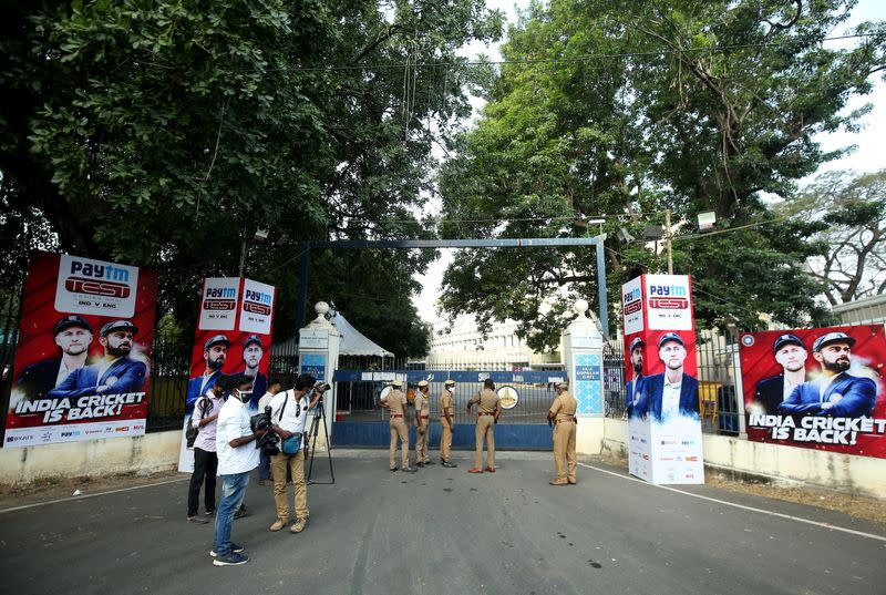 Police officers and members of media stand outside a stadium where India and England play their first test cricket match, in Chennai
