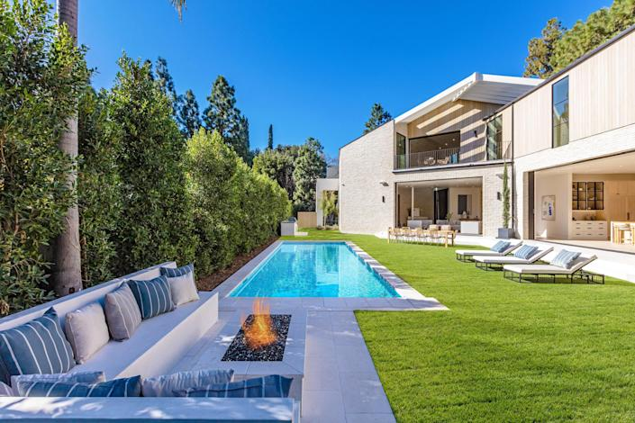 """<p>This bleached-wood-paneled Beverly Hills home masterfully embraces the concept of indoor-outdoor living. The main level features not one but three enormous sliding glass doors that open onto a resort-like pool area complete with a 10-person dining area, a row of chaise longues, and a fire pit with custom banquette seating. The suites on the upper level that overlook the oasis below boast the same large-scale pocket-like glass doors, bringing the freshness of the outdoors inside.</p> <p>Though the multistory mansion is outfitted with all of the fixings of a five-star hotel, including a wine cellar, full gym and spa, and private movie theater with an overhead projector, it's utterly warm courtesy of 11-foot wide steel-case-glass windows through which sunlight floods in. Not to mention that the organic materials throughout, such as the glossy exposed brick that runs from the entryway through one of the casual living spaces, give the home an approachable feel that isn't at all fussy.</p> <p>Price: $17.9 million</p> <p>Beds/Baths: 7 bedrooms, 8 full bathrooms</p> <p>Square Footage: 10,500 square feet</p> <p>For more information, please click <a href=""""https://thewilliamsestates.com/listing/1054-angelo-drive/"""" rel=""""nofollow noopener"""" target=""""_blank"""" data-ylk=""""slk:here"""" class=""""link rapid-noclick-resp"""">here</a>.</p>"""