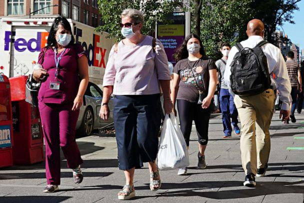 PHOTO: People walk while wearing protective masks as New York City moves into Phase 3 of re-opening following restrictions imposed to curb the coronavirus pandemic, July 14, 2020. (Cindy Ord/Getty Images)