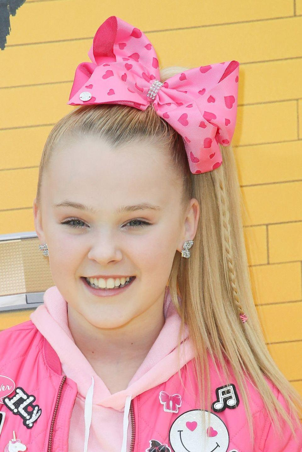 """<p>Now <em>this</em> is how you make an entrance. Copy <strong>JoJo Siwa'</strong>s trademark style by finishing off her ponytail with a massive — key word: massive — bow. </p><p><a class=""""link rapid-noclick-resp"""" href=""""https://www.amazon.com/Alligator-Unicorn-Grosgrain-Barrettes-Accessories%EF%BC%882/dp/B08VRTC5RV/?tag=syn-yahoo-20&ascsubtag=%5Bartid%7C10055.g.3821%5Bsrc%7Cyahoo-us"""" rel=""""nofollow noopener"""" target=""""_blank"""" data-ylk=""""slk:SHOP STATEMENT BOWS"""">SHOP STATEMENT BOWS</a> </p>"""