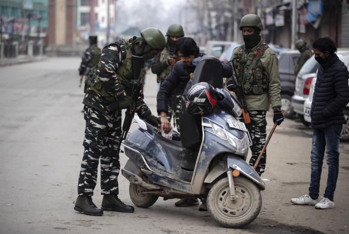 Indian paramilitary soldiers check a scooter of a Kashmiri man in Srinagar, Indian controlled Kashmir, Tuesday, Feb. 9, 2021. Businesses and shops have closed in many parts of Indian-controlled Kashmir to mark the eighth anniversary of the secret execution of a Kashmiri man in New Delhi. Hundreds of armed police and paramilitary soldiers in riot gear patrolled as most residents stayed indoors in the disputed region's main city of Srinagar. (AP Photo/Mukhtar Khan)