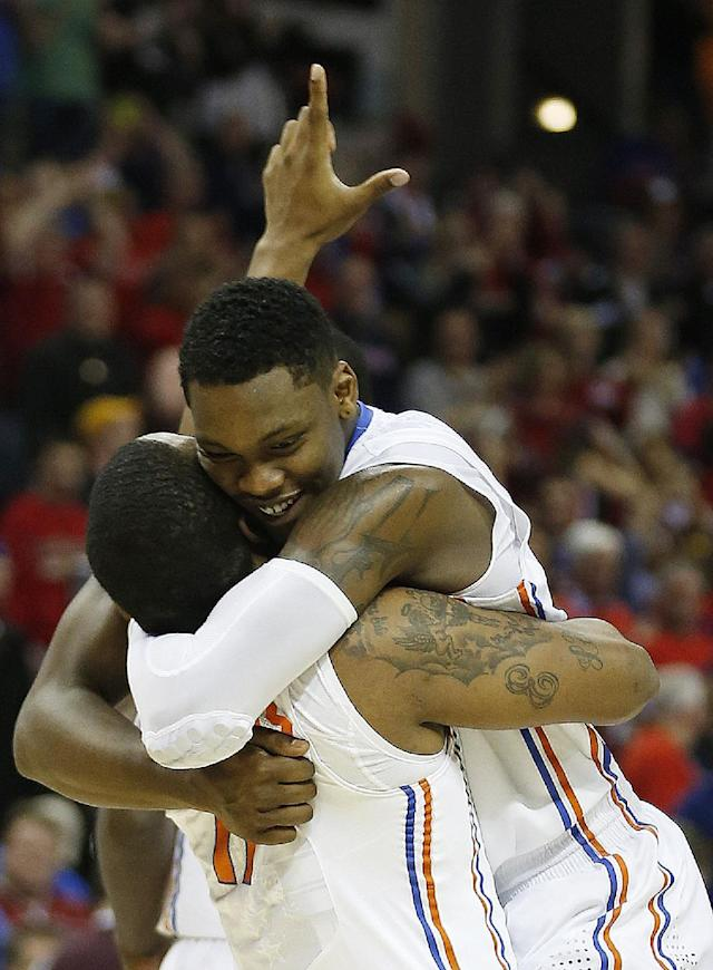 Florida's Lexx Edwards (11) holds Michael Frazier II (20) after the second half in a regional final game against Dayton at the NCAA college basketball tournament, Saturday, March 29, 2014, in Memphis, Tenn. Florida won 62-52. (AP Photo/John Bazemore)