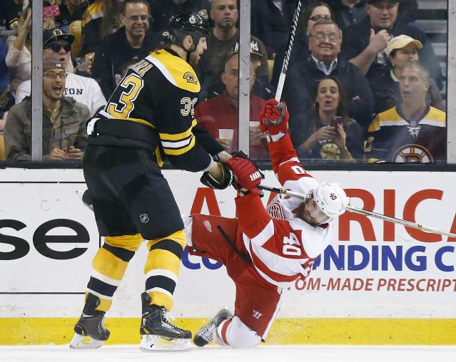 Boston Bruins' Zdeno Chara (33) checks Detroit Red Wings' Henrik Zetterberg (40) during the second period in Game 5 in the first round of the NHL hockey Stanley Cup playoffs in Boston, Saturday, April 26, 2014. (AP Photo/Michael Dwyer)