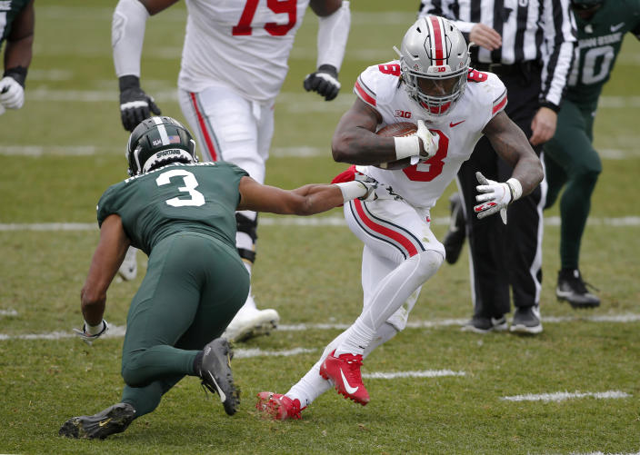Ohio State's Trey Sermon, right, rushes against Michigan State's Xavier Henderson (3) during the first half of an NCAA college football game, Saturday, Dec. 5, 2020, in East Lansing, Mich. Ohio State won 52-12. (AP Photo/Al Goldis)