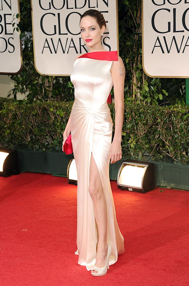 Best all-round Hollywood glam: Angelina Jolie. No leg memes here, but in 2012 Angelina Jolie poured herself into delicious champagne satin with a dashing flap of red at the neckline (although Natalie Portman did a nice twist on that red neckline flap herself). She accessorized the Atelier Versace gown with Lorraine Schwartz earrings and ring, matching red clutch and lipstick, and Brad Pitt with a cane. Jolie's now the standard-bearer an any red carpet, although she gave a hint of that glamour greatness in a 1998 shimmering red-carpet debut.