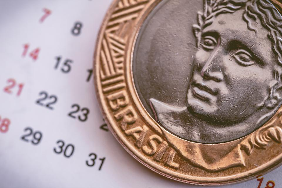 Coin, Real, payment, salary, labor, payment. Brazilian Coin of one Real on a calendar.