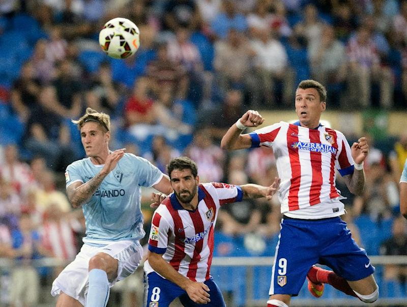 Atletico Madrid's Croatian forward Mario Mandzukic heads to score during the Spanish league football match Club Atletico de Madrid vs S.D Eibar at the Vicente Calderon stadium in Madrid on August 30, 2014