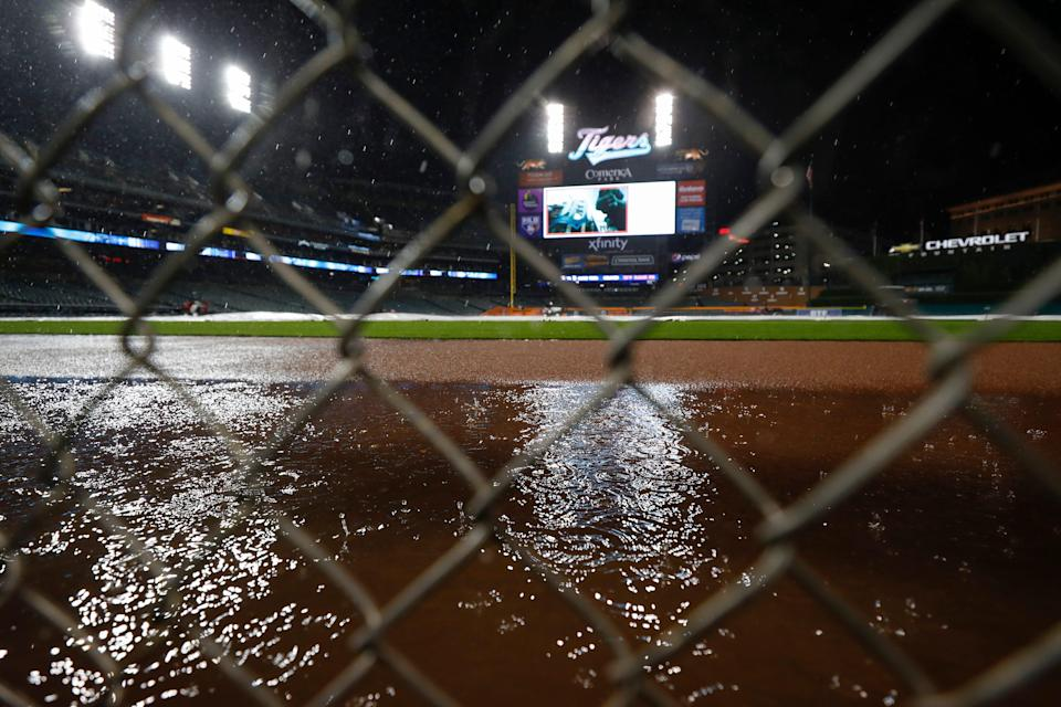 Looking through a fence at a puddle forming on the field during a rain delay in the game between the Tigers and the Brewers on Tuesday, Sept. 14, 2021, at Comerica Park.