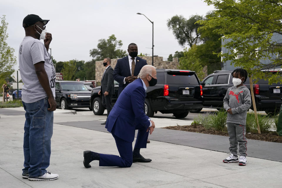 FILE - In this Sept. 9, 2020 file photo, Democratic presidential candidate former Vice President Joe Biden visits with C.J. Brown, right, and Clement Brown, the son and father of the owner of Three Thirteen, as Biden arrives to shop for his grandchildren at the store in Detroit. On Friday, April. 16, 2021, The Associated Press reported on stories circulating online incorrectly claiming a photo shows President Joe Biden kneeling in front of George Floyd's son. (AP Photo/Patrick Semansky)