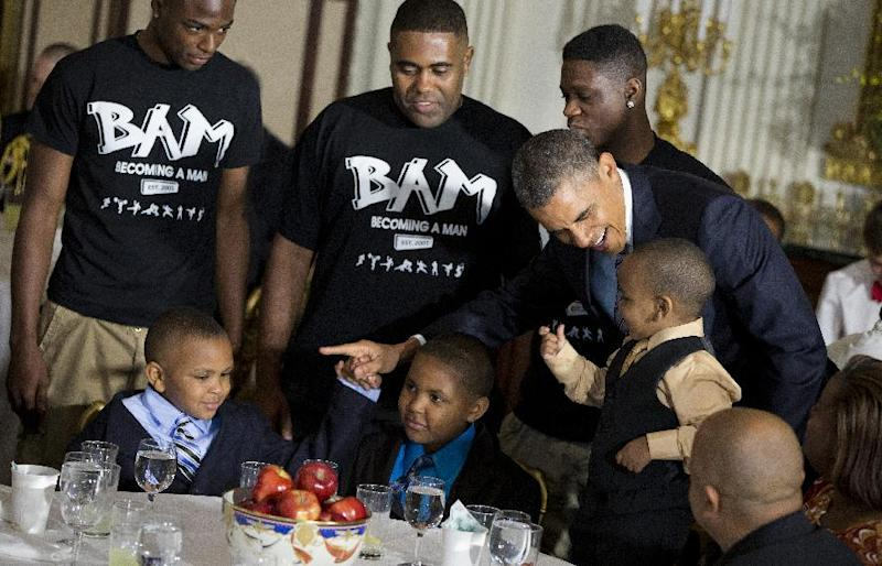 President Barack Obama greets guests, including fathers and their children participants in the Becoming a Man (BAM) program at Hyde Park Academy in Chicago, Friday, June 14, 2013, in the State Dining Room of the White House in Washington, where the president hosted a Father's Day luncheon.  (AP Photo/Evan Vucci)
