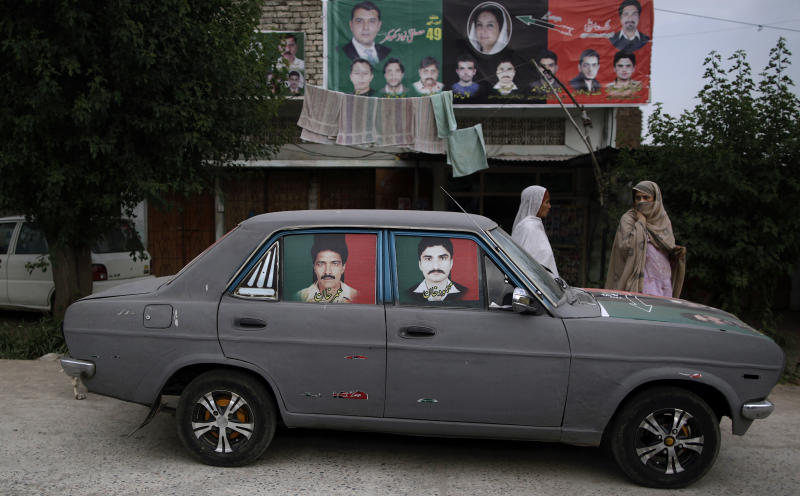 Pakistani women, chat as they walk past a car with posters showing members of Pakistan People's Party, PPP, and back dropped by a banner showing candidates from the PPP for the upcoming parliamentary elections, in a neighborhood in Islamabad, Pakistan, Tuesday, May 7, 2013. Pakistan is scheduled to hold parliamentary elections on May 11, the first transition between democratically elected governments in a country that has experienced three military coups and constant political instability since its creation in 1947. (AP Photo/Muhammed Muheisen)