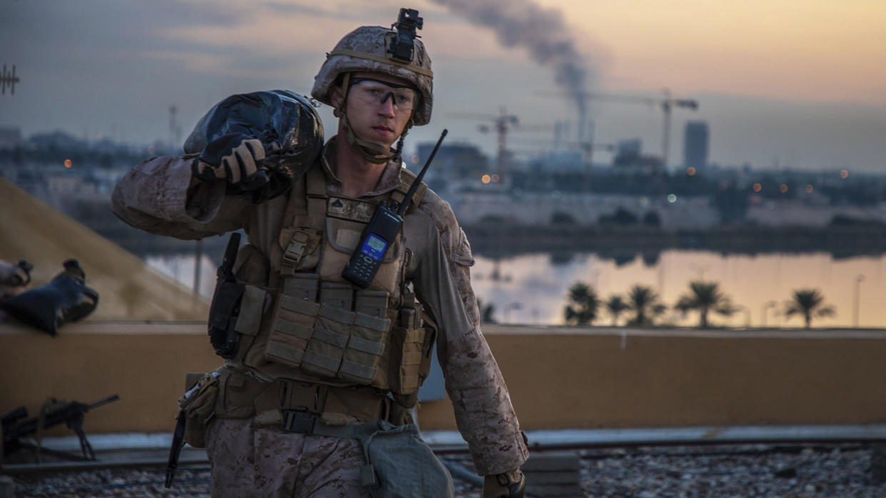 Image: A U.S. Marine with 2nd Battalion, 7th Marines that is part of a quick reaction force, carries a sand bag during the reinforcement of the U.S. embassy compound in Baghdad,