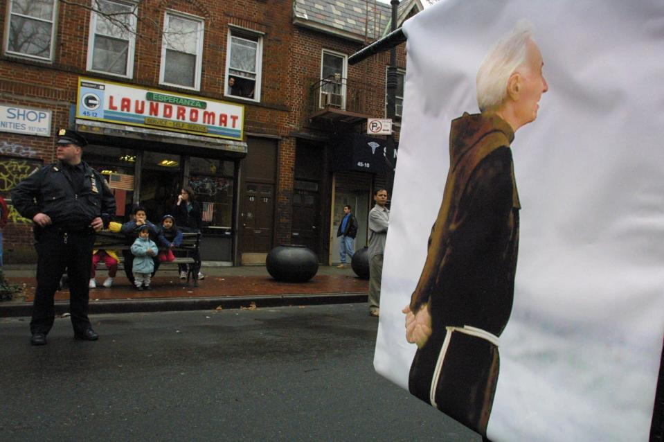 FILE - In this Sunday, March 3, 2002 file photo, a banner printed with a photograph of the late Father Mychal Judge is carried down Skillman Avene in the Queens borough of New York, during an early St. Patrick's Day parade that honored the fire department chaplain killed during the Sept. 11 terrorist attack on the World Trade Center. The third annual parade included groups of various nationalities plus some marchers, such as gays, who would not normally be represented in the city's more traditional parade on March 17th. (AP Photo/Tina Fineberg, File)