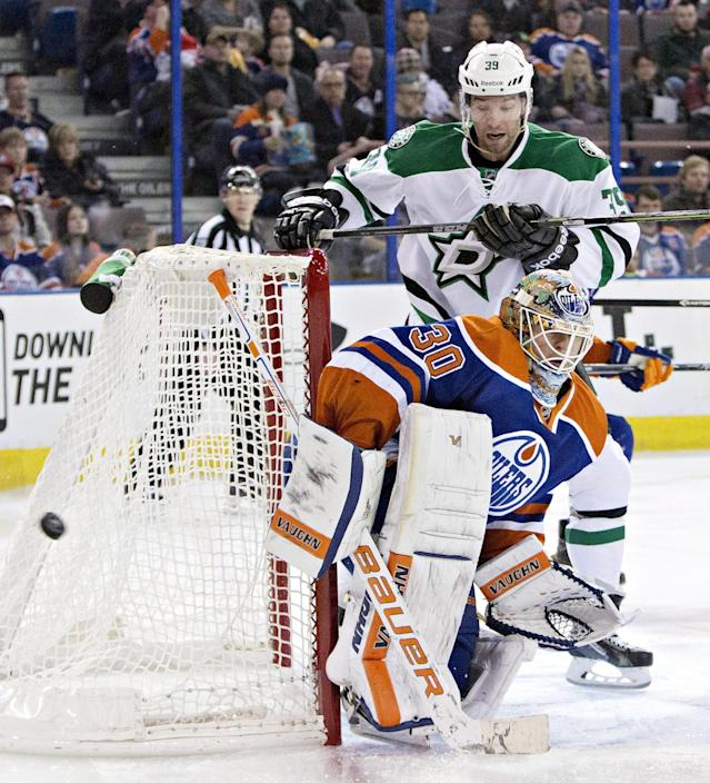 Dallas Stars' Travis Morin (39) looks for the rebound as Edmonton Oilers goalie Ben Scrivens (30) makes the save during the first period of an NHL hockey game in Edmonton, Alberta, on Sunday, Dec. 21, 2014. (AP Photo/The Canadian Press, Jason Franson)