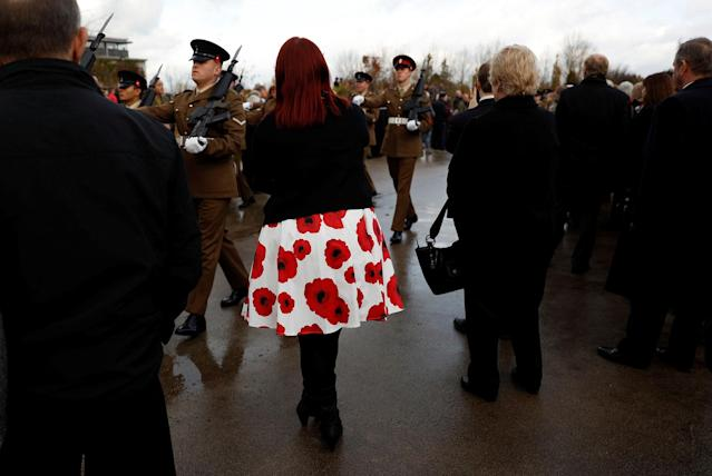 <p>A woman wearing a poppy print dress watches a parade during Armistice Day commemorations at the National Memorial Arboretum in Alrewas, Britain, Nov. 11, 2017. (Photo: Darren Staples/Reuters) </p>