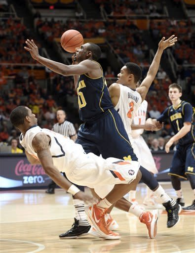 Michigan guard Tim Hardaway Jr. (10) is fouled as he drives between Illinois' Brandon Paul (3) and Joseph Bertrand (2) in the second half of an NCAA college basketball game in Champaign, Ill., on Thursday, March 1, 2012. Michigan won 72-61. (AP Photo/John Dixon)