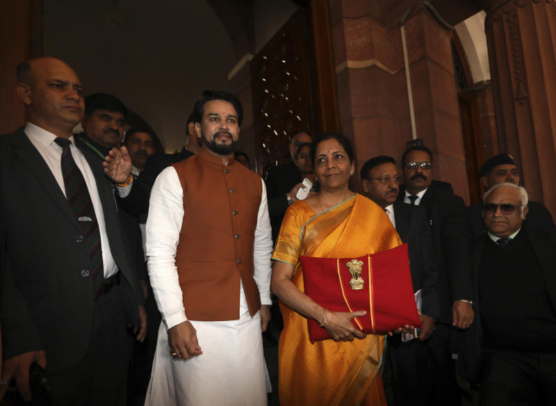 Indian Finance Minister Nirmala Sitharaman, in yellow sari, and junior Finance Minister Anurag Thakur, center left, arrive at the parliament house before presenting the federal budget in New Delhi, India, Saturday, Feb. 1, 2020. India's Hindu nationalist-led government on Saturday offered relief to taxpayers and vowed to spend billions to double farmers' incomes, upgrade infrastructure, health care and industry to boost the lowest economic growth in a decade. (AP Photo/Manish Swarup)