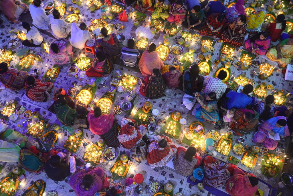 <p>Hundreds of Hindus devotee sits with light candle to celebrate a religious Hindu festival Rakher Upabas at Shamibag Loknath Dham in Dhaka, Bangladesh. Sit in front of candles light and absorb in prayer Lokenath Brahmachari who is called Baba Lokenath was an 18th Century Hindu saint and philosopher in Bengal. Hindu worshippers fast and pray in earnest to the gods for their favors during the traditional ritual called Kartik Brati or Rakher Upobash. (Mamunur Rashid/NurPhoto via Getty Images) </p>