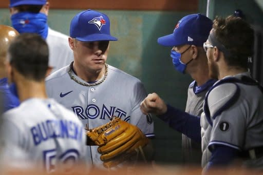 Toronto Blue Jays' Chase Anderson, left, enters the dug out after pitching during the third inning of a baseball game against the Boston Red Sox, Saturday, Aug. 8, 2020, in Boston. (AP Photo/Michael Dwyer)