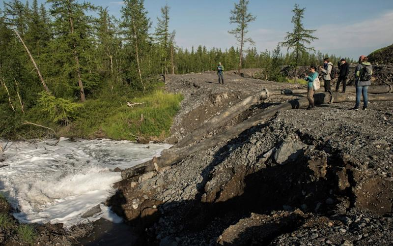 Water from the Norilsk Nickel enrichment plant gushing out of a pipe and into a river - Dmitry Sharomov/Greenpeace via AP