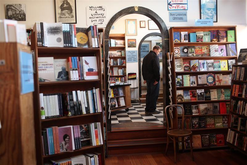 A man looks over a selection of books at City Lights Bookstore in the North Beach neighborhood in San Francisco, California.