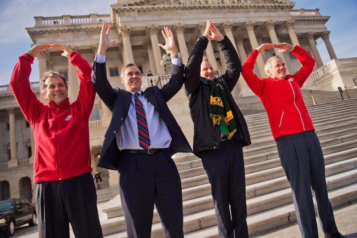 """From left, Sens. Sherrod Brown (D-Ohio), Jeff Merkley (D-Ore.), Ron Wyden (D-Ore.) and Rob Portman (R-Ohio) make symbols that spell """"Ohio"""" on Jan. 13, 2015, as the result of a football bet. Ohio State beat the University of Oregon 42-20 in the NCAA national football championship."""