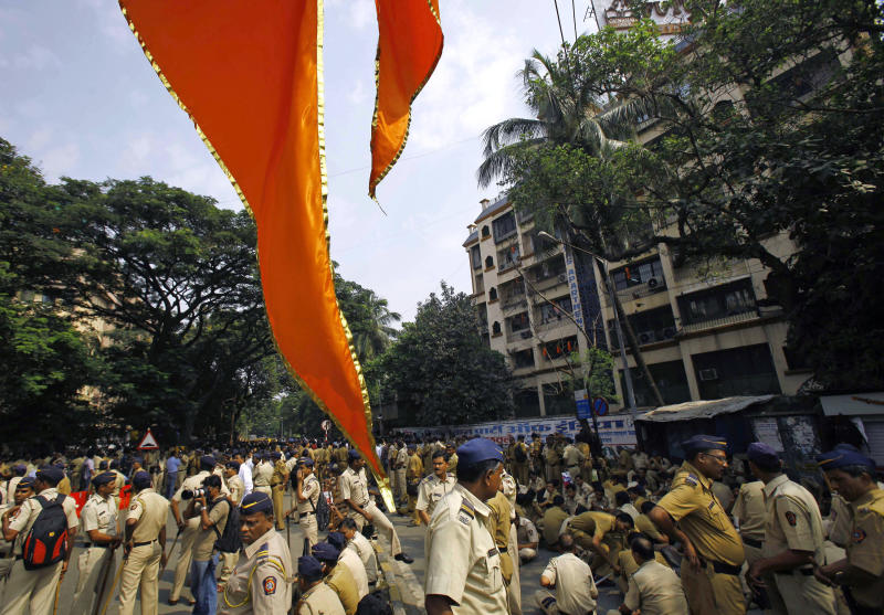 FILE - In this Nov. 15, 2012 file photo, a Shiv Sena flag hangs in the foreground as Indian policemen are deployed outside the residence of Shiv Sena chief Bal Thackeray in Mumbai, India. Indian media say police in Mumbai have arrested two girls who posted a comment on a social networking site criticizing the shutdown of India's financial hub following the death of a Hindu fundamentalist politician over the weekend. (AP Photo/Rafiq Maqbool, File)