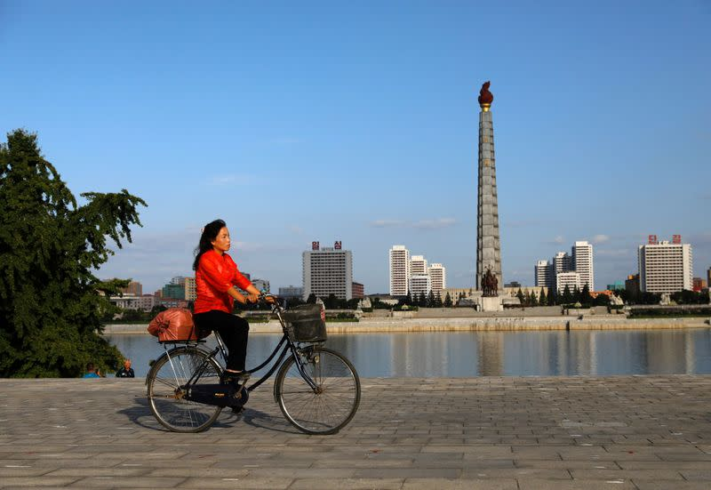 FILE PHOTO: A woman rides a bicycle as Juche Tower is seen in the background along the Taedong river in Pyongyang