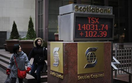 People walk past an electronic board displaying the midday TSX index in Toronto