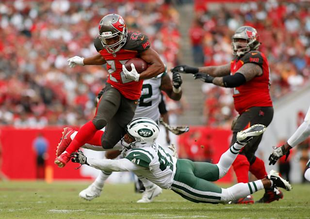 <p>Running back Doug Martin #22 of the Tampa Bay Buccaneers leaps over an tackle attempt by cornerback Buster Skrine #41 of the New York Jets as he runs for a first down during the fourth quarter of an NFL football game on November 12, 2017 at Raymond James Stadium in Tampa, Florida. (Photo by Brian Blanco/Getty Images) </p>