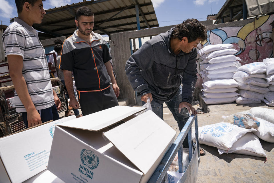 Bags of foodstuffs provided by the United Nations Relief and Works Agency for Palestine Refugees in the Near East (UNRWA) as Palestinians collect food aid following a cease-fire reached after an 11-day war between Gaza's Hamas rulers and Israel, in Gaza City, Saturday, May 22, 2021. (AP Photo/John Minchillo)
