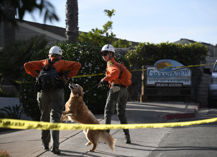 Search and rescue personnel head down to the site of a cliff collapse at a popular beach Friday, Aug. 2, 2019, in Encinitas, Calif. At least one person was reportedly killed, and multiple people were injured, when an oceanfront bluff collapsed Friday at Grandview Beach in the Leucadia area of Encinitas, authorities said. (AP Photo/Denis Poroy)