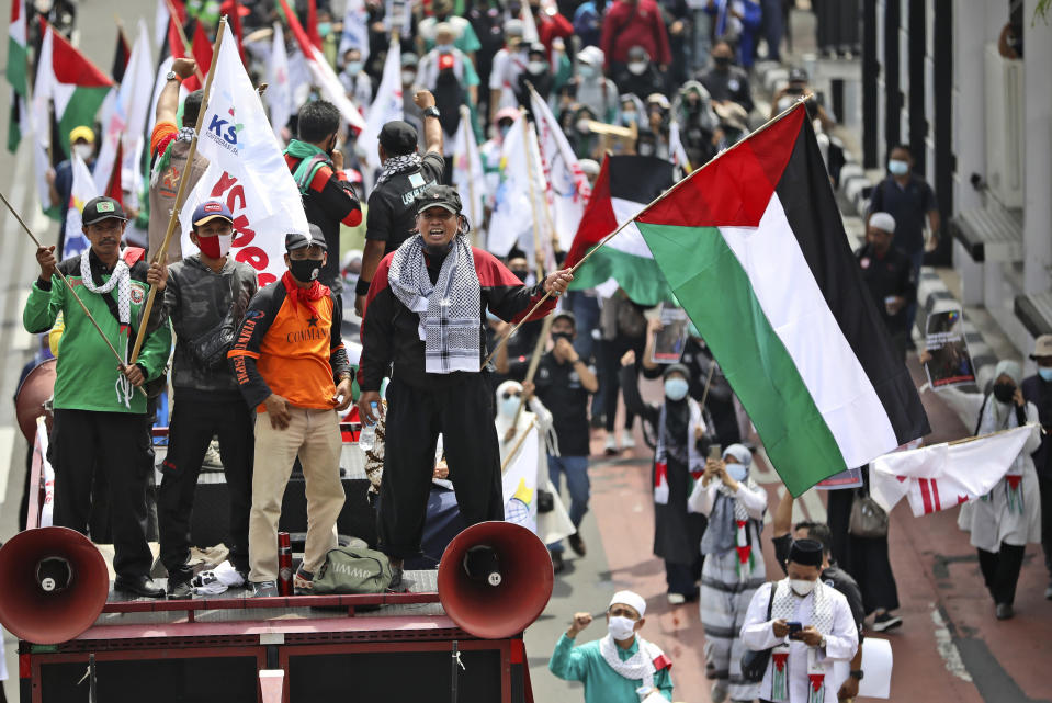A labor activist holds a Palestinian flag as he shouts slogans during a rally condemning Israeli attacks on the Palestinians, in Jakarta, Indonesia, Tuesday, May 18, 2021. (AP Photo/Dita Alangkara)