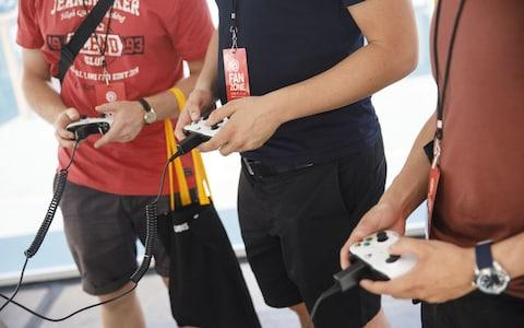 Attendees hold Microsoft Corp. Xbox One controllers while playing during a UbiSoft Entertainment SA event - Credit: Patrick T. Fallon/Bloomberg