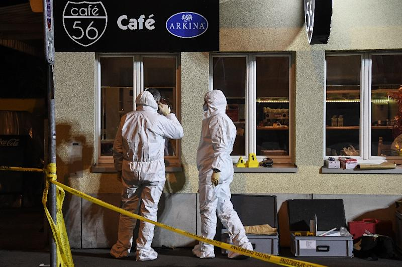 Police collect evidence at the site of a shooting in the Swiss city of Basel on March 9, 2017 which left two people dead and one seriously injured