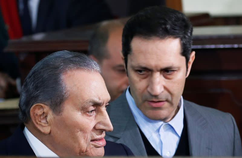 Former Egyptian President Hosni Mubarak arrives with his son Alaa in a court case accusing ousted Islamist president Mohamed Mursi of breaking out of prison in 2011, in Cairo